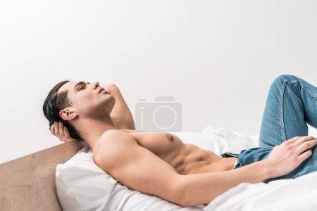 Photo pour Bel homme torse nu dans des jeans se trouvant sur le lit à la maison - image libre de droit
