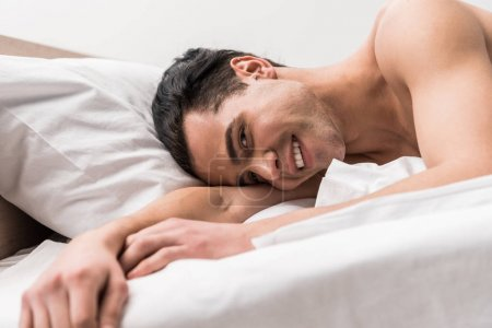 Photo for Low angle view of happy man looking at camera while lying on bed - Royalty Free Image