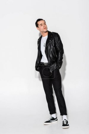 Photo for Handsome man in leather jacket standing with hands in pockets on white - Royalty Free Image