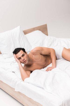 Photo pour Homme musculaire et torse nu sérieux regardant l'appareil-photo et se trouvant sur le lit - image libre de droit