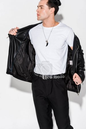 Photo for Stylish man taking off leather jacket while standing on white - Royalty Free Image