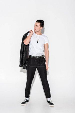 Foto de Hombre guapo en camiseta blanca sosteniendo chaqueta de cuero mientras que de pie en blanco - Imagen libre de derechos