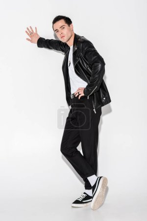 Photo for Handsome man in black leather jacket standing with crossed legs on white - Royalty Free Image
