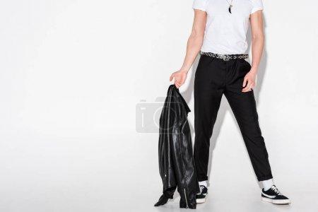 Photo pour Homme recadré de vue dans le t-shirt blanc retenant la veste en cuir noir sur le blanc - image libre de droit