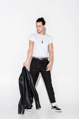 Photo for Man in white t-shirt looking at black leather jacket on white - Royalty Free Image