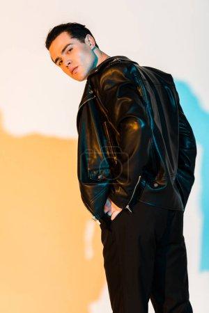 Photo pour Bel homme dans la veste en cuir noir restant et regardant l'appareil-photo sur le blanc avec l'illumination - image libre de droit