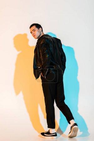Photo pour Bel homme dans la veste en cuir noir restant avec la main dans la poche et regardant l'appareil-photo sur le blanc avec l'illumination - image libre de droit