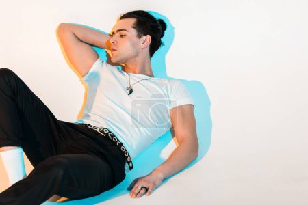 Photo for Pensive man in white t-shirt lying on white with illumination - Royalty Free Image