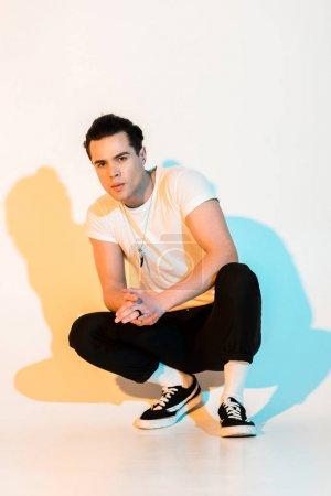 Photo pour Bel homme dans le t-shirt blanc se reposant avec les mains serrées sur le blanc avec l'illumination - image libre de droit