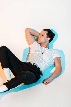Photo pour Bel homme en t-shirt blanc couché sur blanc avec éclairage - image libre de droit
