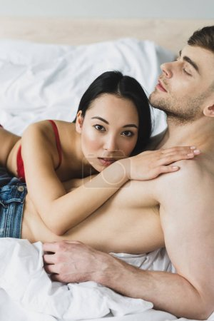 Foto de Beautiful asian woman looking at camera while lying on chest of handsome boyfriend - Imagen libre de derechos