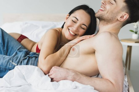 Photo for Cheerful asian woman lying on chest of happy shirtless boyfriend - Royalty Free Image