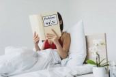 "Постер, картина, фотообои ""young woman reading problems in sex book while lying in bed"""