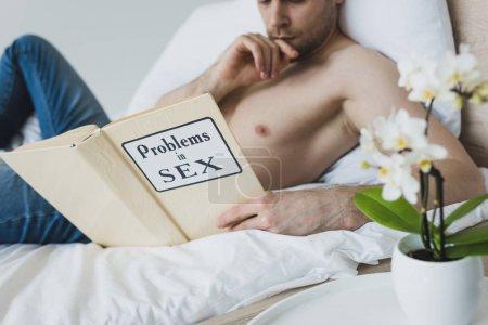 Photo pour Foyer sélectif des problèmes de lecture d'homme torse nu dans le livre de sexe tout en se trouvant dans le lit - image libre de droit