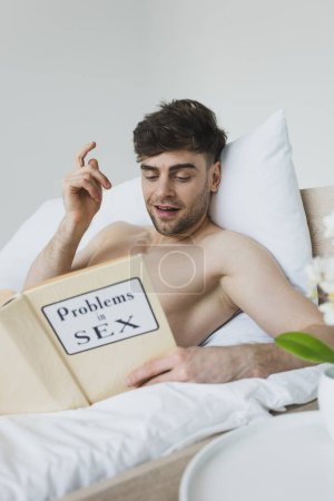 Photo for Cheerful man showing idea sign while reading problems in sex book - Royalty Free Image