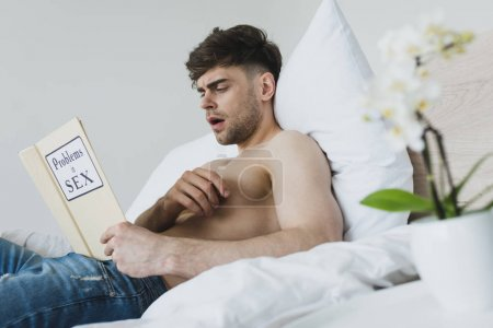 Photo for Shocked handsome man reading problems in sex book while lying on white bedding - Royalty Free Image