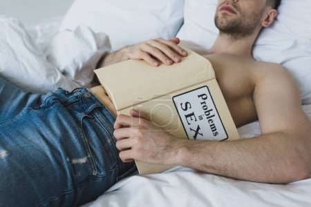 Photo for Partial view of shirtless man holding problems in sex book while lying on white bedding in blue jeans - Royalty Free Image