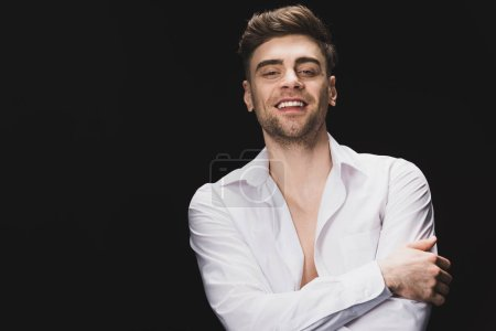 Photo for Cheerful handsome man in white shirt smiling and looking at camera isolated on black - Royalty Free Image
