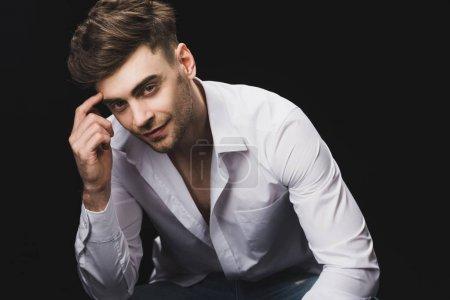 Foto de Positivo hombre guapo en camisa blanca mirando la cámara aislada en negro - Imagen libre de derechos