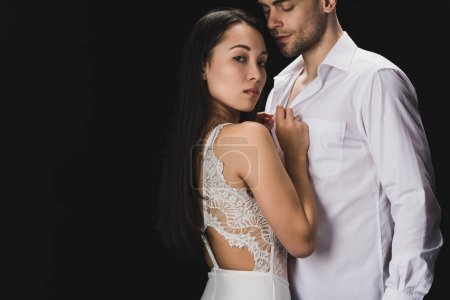 Photo for Attractive asian woman in white lingerie standing near boyfriend and looking at camera isolated on black - Royalty Free Image