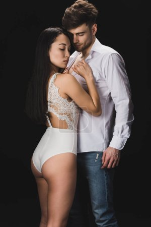 Foto de Sexy asian woman in white lingerie standing near boyfriend and looking at camera isolated on black - Imagen libre de derechos