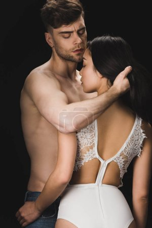 Photo for Young shirtless man hugging sexy girlfriend in white lingerie isolated on black - Royalty Free Image