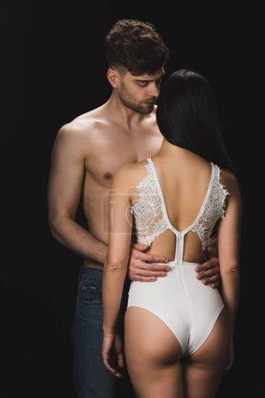 Photo pour Homme torse nu beau étreignant la petite amie sexy dans la lingerie blanche d'isolement sur le noir - image libre de droit