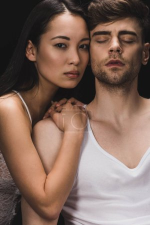 Photo for Attractive asian woman lying on shoulder of handsome boyfriend and looking at camera isolated on black - Royalty Free Image