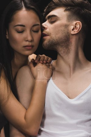 Photo for Handsome man kissing beautiful asian woman lying on his shoulder isolated on black - Royalty Free Image