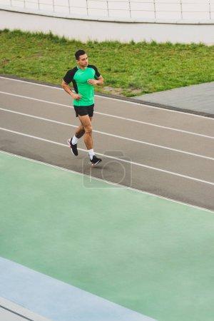 Photo pour Vue de pleine longueur du sportif de course mélangé fonctionnant au stade - image libre de droit