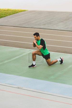 Photo pour Sportif de course mixte dans sportswear s'étendant au stade - image libre de droit
