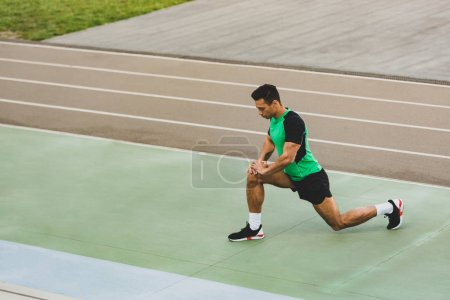 Photo for Mixed race sportsman in sportswear stretching at stadium - Royalty Free Image