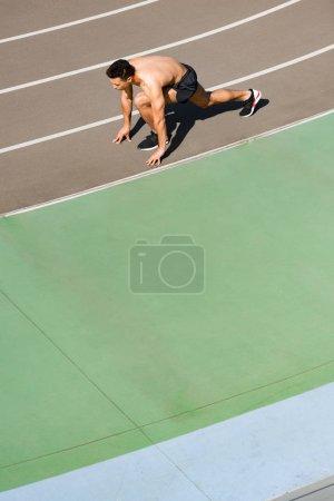 Photo pour Vue aérienne d'un sportif de course mixte se préparant à courir au stade - image libre de droit