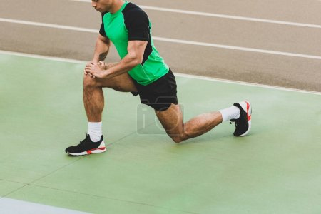 Photo for Cropped view of mixed race sportsman stretching at stadium - Royalty Free Image