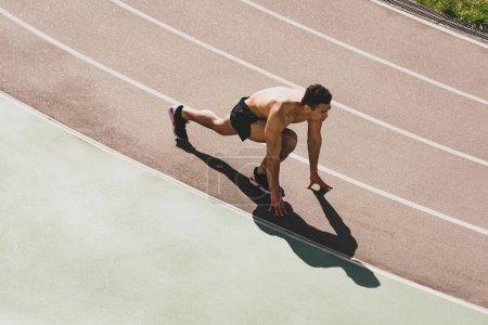 Photo pour Overhead view of mixed race sportsman preparing to run at stadium - image libre de droit