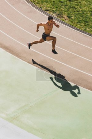 Photo for Overhead view of mixed race sportsman running at stadium - Royalty Free Image