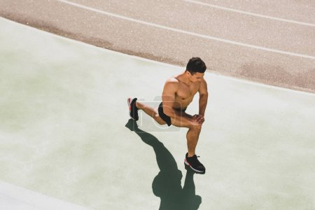 Photo for Overhead view of shirtless mixed race sportsman stretching at stadium - Royalty Free Image