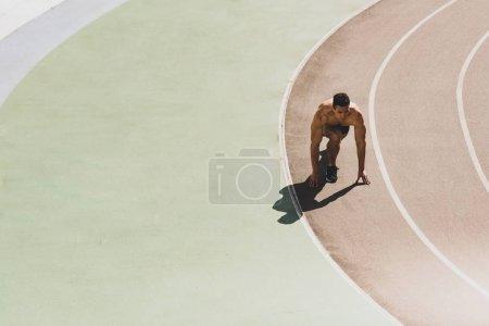 Photo pour Sportif de course mixte se préparant à courir au stade - image libre de droit