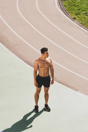 Photo for Full length view of mixed race sportsman standing at stadium - Royalty Free Image
