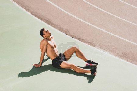 Photo pour Beau sportif de course mixte fatigué s'asseyant au stade - image libre de droit