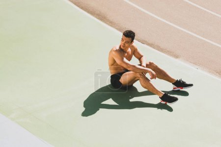 Photo for Tired handsome mixed race sportsman sitting at stadium - Royalty Free Image