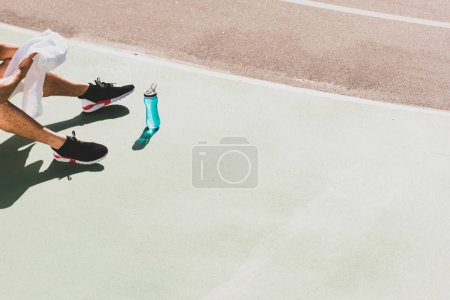 Photo for Cropped view of sportsman with towel and sport bottle sitting at stadium - Royalty Free Image