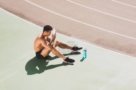 Photo for Mixed race sportsman sitting at stadium and wiping face with towel - Royalty Free Image