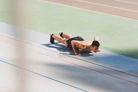 Photo for Shirtless mixed race sportsman doing push ups at stadium - Royalty Free Image