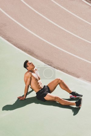 shirtless mixed race sportsman sitting at stadium with closed eyes
