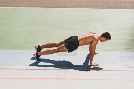 Photo for Mixed race sportsman standing in plank at stadium - Royalty Free Image