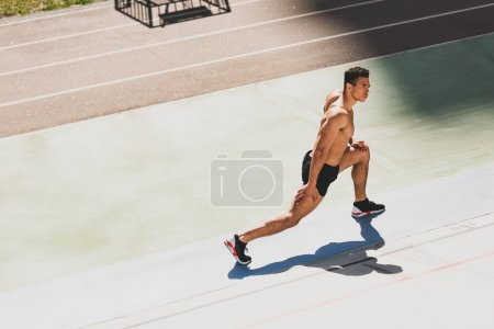 Photo for Shirtless mixed race sportsman in black sneakers stretching at stadium - Royalty Free Image