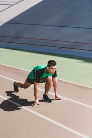 Photo for Mixed race sportsman preparing to run at stadium - Royalty Free Image