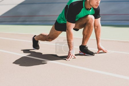 Photo for Cropped view of sportsman preparing to run at stadium - Royalty Free Image