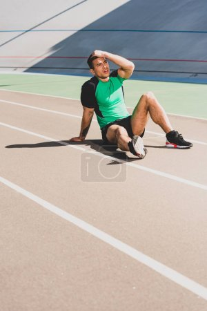 Photo for Tired mixed race sportsman sitting at stadium and touching head - Royalty Free Image